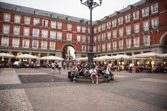 Οι άνθρωποι κάθονται κάτω από ένα lamppost στο δήμαρχο της Μαδρίτης ` s Plaza Στοκ εικόνες με δικαίωμα ελεύθερης χρήσης