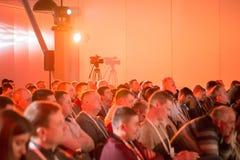 οι άνθρωποι κάθονται στην αίθουσα κάτω από την πηγή κόκκινου φωτός Στοκ φωτογραφία με δικαίωμα ελεύθερης χρήσης