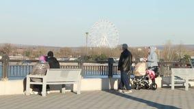 Οι άνθρωποι κάθονται στις καρέκλες στο ανάχωμα και το ρολόι στο κυανό νερό της Μαύρης Θάλασσας απόθεμα βίντεο