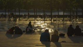Οι άνθρωποι κάθονται τη στήριξη κοντά στην πηγή στο ηλιοβασίλεμα απόθεμα βίντεο
