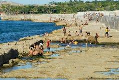 Οι άνθρωποι κάνουν ηλιοθεραπεία στο Malecon seawall στην Αβάνα, Κούβα Στοκ Εικόνες