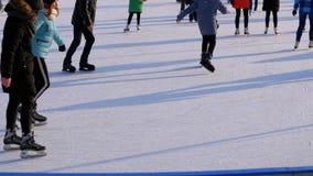 Οι άνθρωποι κάνουν πατινάζ στην αίθουσα παγοδρομίας πάγου στην ηλιόλουστη ημέρα κίνηση αργή απόθεμα βίντεο