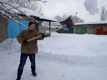 Οι άνθρωποι καθαρίζουν μακριά τα φτυάρια χιονιού μετά από τις βαριές χιονοπτώσεις στοκ εικόνες