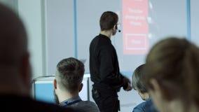 Οι άνθρωποι κοιτάζουν δεδομένου ότι ο ομιλητής λέει την ενδιαφέρουσα ομιλία στην επιχειρησιακή διάσκεψη απόθεμα βίντεο