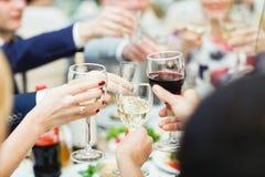 Οι άνθρωποι κρατούν στα γυαλιά χεριών με το άσπρο και κόκκινο κρασί Στοκ φωτογραφία με δικαίωμα ελεύθερης χρήσης
