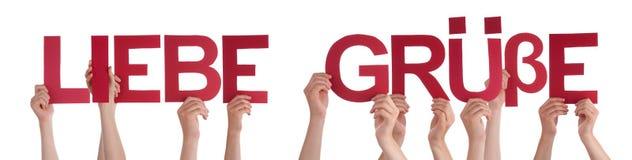 Οι άνθρωποι κρατούν ότι το ευθύ Word Liebe Gruesse σημαίνει την αγάπη Στοκ φωτογραφίες με δικαίωμα ελεύθερης χρήσης