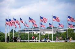 Οι άνθρωποι μεταξύ των σημαιών του μνημείου της Ουάσιγκτον είναι ένας οβελίσκος Στοκ Φωτογραφία