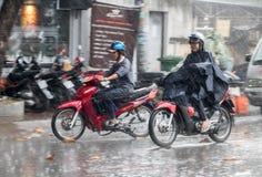 Οι άνθρωποι με ένα αδιάβροχο οδηγούν σε μια μοτοσικλέτα στη βροχή στοκ φωτογραφίες