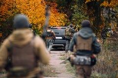 Οι άνθρωποι με τα πυροβόλα όπλα ακολουθούν το αυτοκίνητο Εκλεκτική εστίαση στοκ φωτογραφίες
