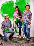 Οι άνθρωποι ομάδας χρωματίζουν τον τοίχο στο σπίτι Στοκ Φωτογραφίες