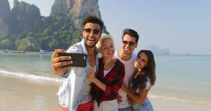 Οι άνθρωποι ομαδοποιούν σχετικά με την παραλία που παίρνει τη φωτογραφία Selfie στο έξυπνο τηλέφωνο κυττάρων αγκαλιάζοντας τους ε απόθεμα βίντεο
