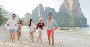 Οι άνθρωποι ομαδοποιούν το τρέξιμο στην παραλία πέρα από τους ευτυχείς χαμογελώντας τουρίστες νεαρών άνδρων και γυναικών βουνών σ απόθεμα βίντεο