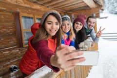 Οι άνθρωποι ομαδοποιούν τη λήψη του έξυπνου θερέτρου χειμερινών βουνών πεζουλιών τηλεφωνικών ξύλινου εξοχικών σπιτιών φωτογραφιών Στοκ Εικόνα