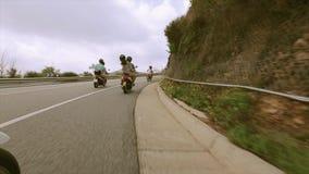 Οι άνθρωποι πίσω πλευράς στα κράνη οδηγούν στη μοτοσικλέτα στο δρόμο στο σύνολο βουνών των πράσινων δέντρων ταξίδι απόθεμα βίντεο