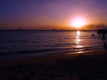 Οι άνθρωποι παίζουν στο νερό με το δραματικό ηλιοβασίλεμα στην παραλία Kaimana Στοκ εικόνα με δικαίωμα ελεύθερης χρήσης