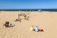 Οι άνθρωποι παίζουν την πετοσφαίριση και το τραίνο στην παραλία Στοκ Φωτογραφίες