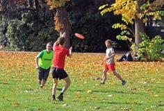 Οι άνθρωποι παίζουν το frisbee στο πάρκο πόλεων Στοκ Φωτογραφία