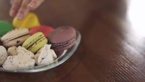 Οι άνθρωποι παίρνουν ζωηρόχρωμα macaroons από το πιάτο απόθεμα βίντεο