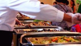Οι άνθρωποι παίρνουν τα τρόφιμα στον πίνακα μπουφέδων απόθεμα βίντεο