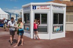 Οι άνθρωποι παίρνουν τους χάρτες και τις κατευθύνσεις στο γραφείο του θαλάμου τουρισμού στο Μονακό στοκ εικόνες