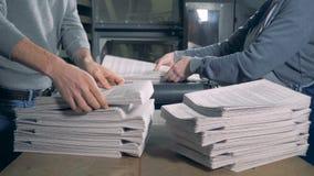 Οι άνθρωποι παίρνουν το τυπωμένο έγγραφο από έναν μεταφορέα τυπογραφίας φιλμ μικρού μήκους