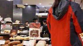 Οι άνθρωποι παρατάσσουν για την αγορά του ψωμιού μέσα στο κινεζικό κατάστημα κέικ και ψωμιού απόθεμα βίντεο