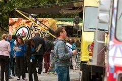 Οι άνθρωποι περιμένουν στη γραμμή να αγοράσουν τα γεύματα από τα φορτηγά τροφίμων στοκ φωτογραφίες