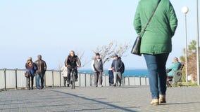 Οι άνθρωποι περπατούν κατά μήκος του αναχώματος κοντά στη θάλασσα απόθεμα βίντεο