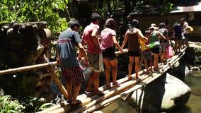 Οι άνθρωποι περπατούν κατά μήκος του σωρού της γέφυρας για πεζούς μπαμπού φιλμ μικρού μήκους