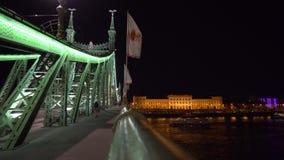 Οι άνθρωποι περπατούν στη γέφυρα ελευθερίας που φωτίζεται τη νύχτα απόθεμα βίντεο