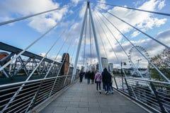 Οι άνθρωποι περπατούν στις χρυσές γέφυρες για πεζούς ιωβηλαίου βασίλισσας ` s Στοκ Εικόνες