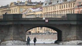 Οι άνθρωποι περπατούν στον πάγο του παγωμένου καναλιού κάτω από τη γέφυρα φιλμ μικρού μήκους