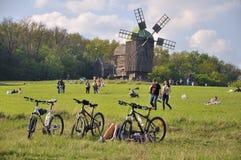 Οι άνθρωποι περπατούν, φύση, παλαιός μύλος, ποδήλατα στο πρώτο πλάνο Στοκ φωτογραφία με δικαίωμα ελεύθερης χρήσης