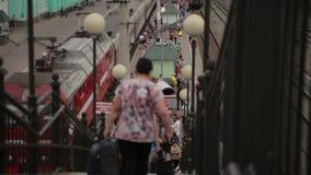 Οι άνθρωποι πηγαίνουν κάτω στα σκαλοπάτια σταθμών τρένου φιλμ μικρού μήκους