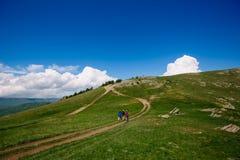 Οι άνθρωποι πηγαίνουν στα βουνά Οι τουρίστες ανεβαίνουν το λόφο κατά μήκος του ίχνους Το οροπέδιο στο βουνό Σαφής καιρός στα βουν Στοκ Εικόνες