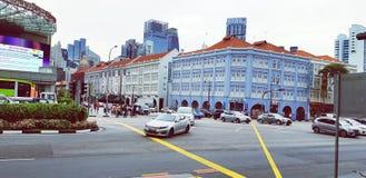 Οι άνθρωποι που περιμένουν τα αυτοκίνητα σταματούν για να διασχίζουν την οδό στην πόλη με το παλαιό μπλε υπόβαθρο ύφους οικοδόμησ στοκ φωτογραφίες