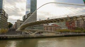 Οι άνθρωποι που περπατούν πέρα από την κατασκευή γυαλιού Zubizuri γεφυρώνουν στο Μπιλμπάο, Ισπανία απόθεμα βίντεο