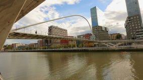 Οι άνθρωποι που περπατούν πέρα από το σύγχρονο γυαλί Zubizuri γεφυρώνουν στο Μπιλμπάο, Ισπανία απόθεμα βίντεο