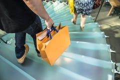 Οι άνθρωποι που περπατούν σε ένα γυαλί κινούνται σπειροειδώς σκάλα Στοκ εικόνα με δικαίωμα ελεύθερης χρήσης