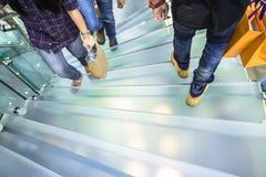 Οι άνθρωποι που περπατούν σε ένα γυαλί κινούνται σπειροειδώς σκάλα Στοκ φωτογραφία με δικαίωμα ελεύθερης χρήσης