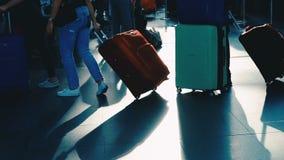 Οι άνθρωποι που περπατούν στον αερολιμένα διέρχονται το τερματικό με τις αποσκευές αποσκευών που πηγαίνουν στο ταξίδι ή το επαγγε φιλμ μικρού μήκους