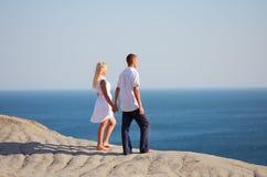Οι άνθρωποι που στέκονται στο λόφο και εξετάζουν τη θάλασσα στοκ εικόνα με δικαίωμα ελεύθερης χρήσης