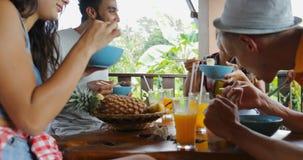 Οι άνθρωποι που τρώνε τα εύγευστα ασιατικά τρόφιμα νουντλς, ομάδα φίλων κάθονται στον πίνακα στο πεζούλι με την άποψη σχετικά με  απόθεμα βίντεο