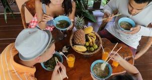 Οι άνθρωποι που τρώνε τα εύγευστα ασιατικά τρόφιμα σούπας νουντλς, τροφή ομάδας φίλων μεταξύ τους κάθονται στην άποψη γωνίας επιτ απόθεμα βίντεο