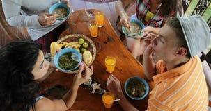 Οι άνθρωποι που τρώνε τα εύγευστα ασιατικά τρόφιμα σούπας νουντλς, τροφή ομάδας φίλων μεταξύ τους κάθονται στην άποψη γωνίας επιτ φιλμ μικρού μήκους