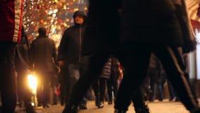 Οι άνθρωποι ρέουν κατά μήκος μιας αναμμένης οδού Γιρλάντες Χριστουγέννων πλήθος απόθεμα βίντεο