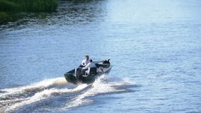 Οι άνθρωποι σε μια γρήγορη βάρκα μηχανών πλέουν κατά μήκος του ποταμού σε σε αργή κίνηση φιλμ μικρού μήκους