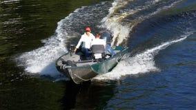 Οι άνθρωποι σε μια γρήγορη βάρκα μηχανών πλέουν κατά μήκος του ποταμού σε σε αργή κίνηση απόθεμα βίντεο