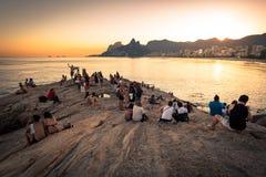 Οι άνθρωποι σε Arpoador λικνίζουν το ηλιοβασίλεμα προσοχής Στοκ Φωτογραφία