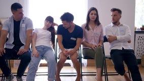Οι άνθρωποι σκέφτονται για κάτι με τις διαφορετικές συγκινήσεις στα πρόσωπα που κάθονται στη σειρά μετά από τη συνεδρίαση της θερ απόθεμα βίντεο